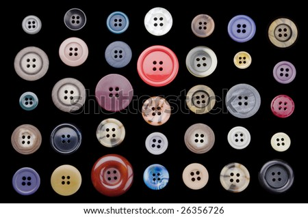 A variety of old buttons neatly arranged on a black background. - stock photo