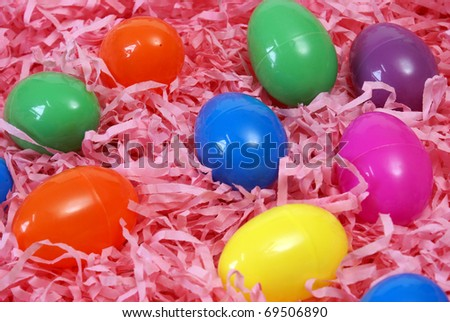 A variety of plastic Easter eggs on pink paper shreds.