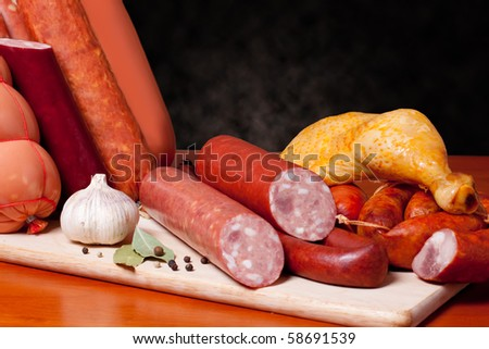 A variety of processed cold meat products, on a wooden cutting board. - stock photo