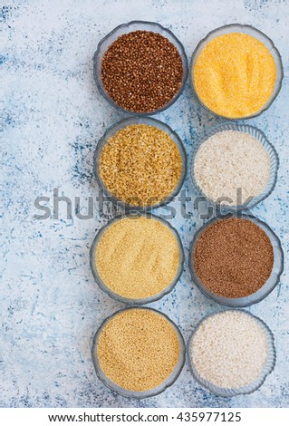 A variety of raw cereal and grains bowl. Rice, couscous, quinoa, bulgur, cormeal, cornflour, buckwheat. Vegetarian food. op view. rustic pastel style. - stock photo