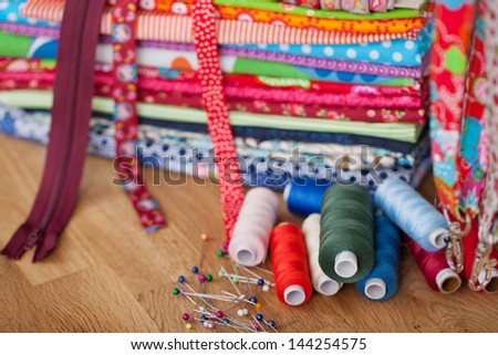 A variety of sewing utensils like pins, thread, ribbon and zipper. - stock photo