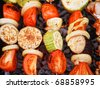 A variety of skewered meats and vegetables cooking on the grill - stock photo