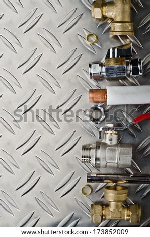 A variety Plumbing inlet pipe valve on a metal surface - stock photo