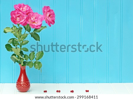 A Vase of pink Roses on blue background  with copy space. - stock photo
