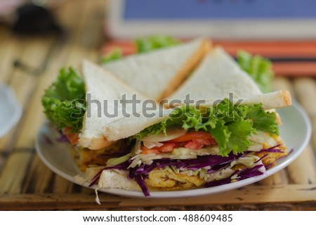 a vegetable triangle Sandwiches and crisps on a wooden table in a restaurant