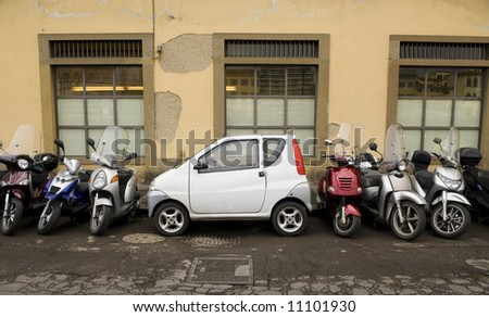 A vehicle is wedged between several motorcycles on the streets of Florence, Italy. - stock photo