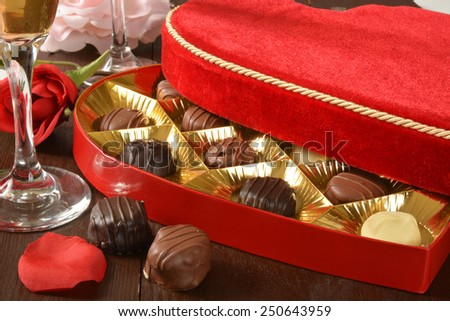 A velvet box of gourmet Valentines Day chocolates with champagne - stock photo