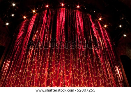 A velvet red theater curtain with traces of gold - stock photo