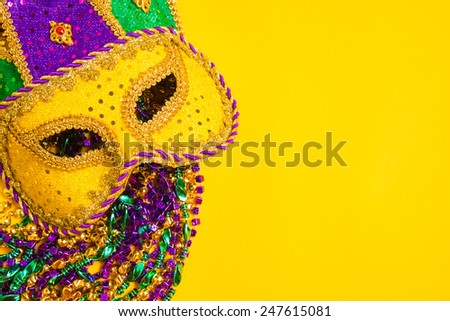 A venetian, mardi gras mask or disguise on a yellow background - stock photo
