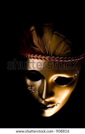 A venetian mask decorated with feathers and stars isolated against a black background