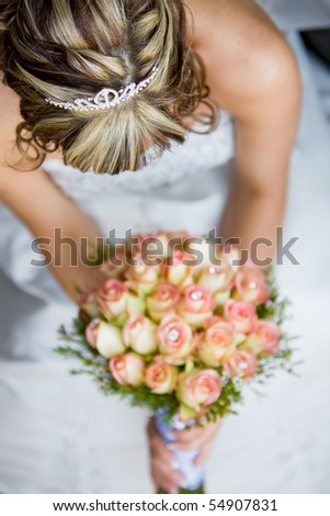 A vertical image of a caucasian bride holding her rose bouquet, photographed from above to show her hair.