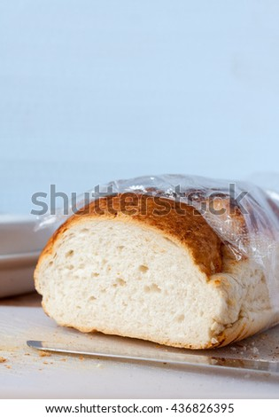 A vertical image of a freshly cut tiger bloomer bread loaf on a white chopping board with a blue background - stock photo