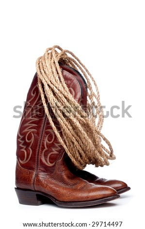 a vertical image of a pair of brown cowboy boots and a coil of rope on a white background - stock photo
