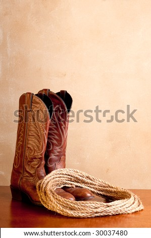 a vertical image of a pair of brown cowboy boots and a coil of rope on a wooded surface with an old textured background - stock photo