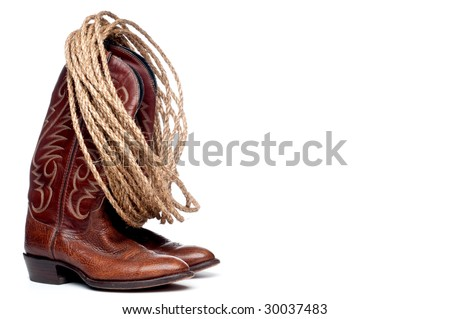 a vertical image of a pair of brown cowboy boots and a coil of rope on white - stock photo