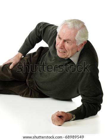 A vertical image of a senior man on the ground who has injured his hip in a fall.  Isolated on white. - stock photo
