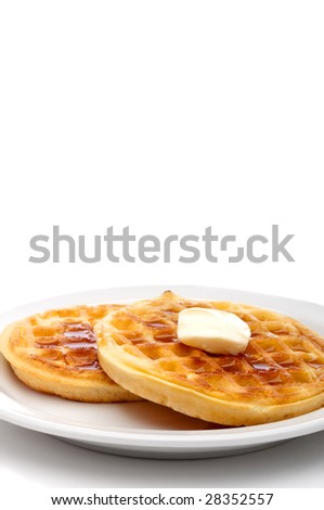 A vertical image of two frozen breakfast waffles with a pat of butter and maple syrup on a white plate with space for copy - stock photo