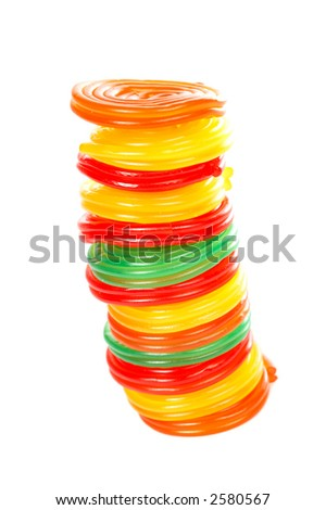 A vertical pile of pieces of multicolored licorices on white background - stock photo