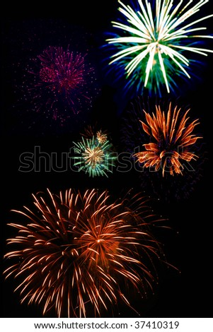 A vertical shot of fireworks in a nighttime sky - stock photo