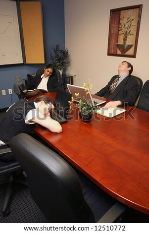 A vertical shot of two businesswomen and a businessman asleep in a conference room. - stock photo