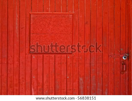 A vertical slat red barn door with lock on it. - stock photo