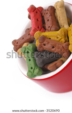 A vertically framed bowl of dog bone treats. Over pure white for your copy. - stock photo