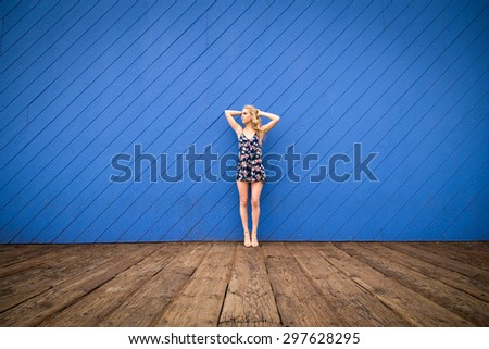 A very attractive woman stands in front of an wooden bright blue wall. She is looking to the side. She is a California girl with long blond hair. - stock photo