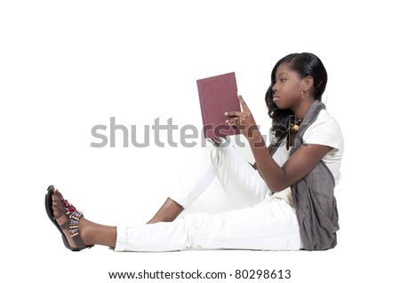 A very beautiful African American black woman teenage student reading a book - stock photo
