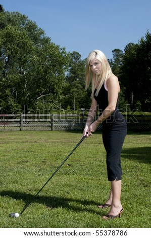 A very beautiful and young female golfer - stock photo