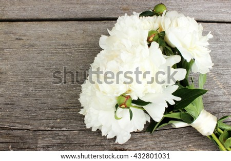 A very beautiful bouquet of fresh white peony on old grey wooden background. Floral decor elements. Copy space.