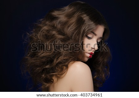 a very beautiful girl model with lush hair and creative make-up on blue background