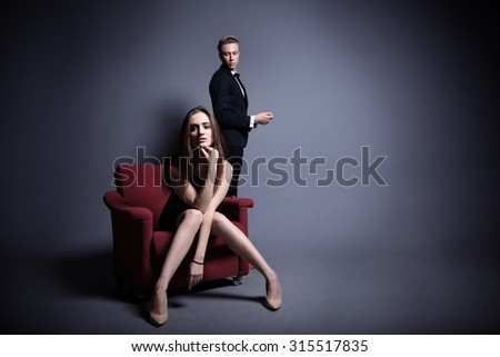 A very beautiful woman is posing with a handsome man in the dark studio in different clothes - stock photo