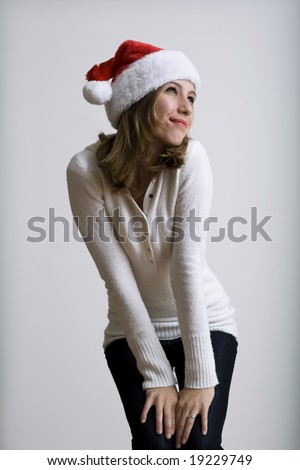 A very beautiful young model smiling while posing in a santa hat - stock photo