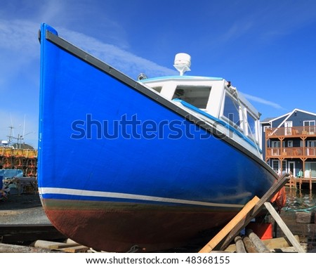 A very blue fishing boat in dock - stock photo