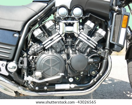 A very clean 4 cylinder motorcycle engine on a parking lot.
