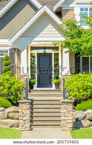 A very clean entrance of a house with a nice lawn and outdoor landscape - stock photo