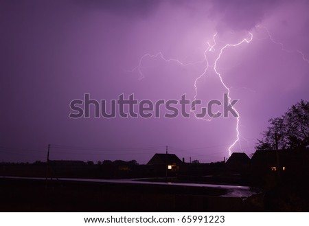A very clear and detailed lightning bolt hits a small hill - stock photo