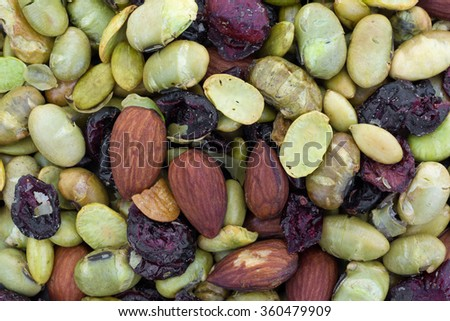 A very close view of dry roasted edamame with dried cranberries and blueberries plus almonds and pumpkin seeds.