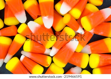 A very close view of Halloween candy corn kernels on a dark background. - stock photo