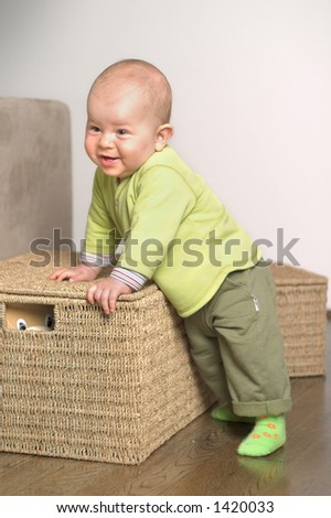 A very cute 8-9 months old baby is playing with teddy bears in a basket.