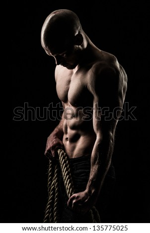 a very fit yuong male holding a thick rope - stock photo