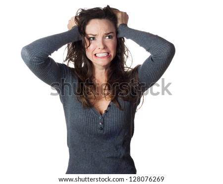 A very frustrated and angry woman pulling her hair. Isolated on white. - stock photo
