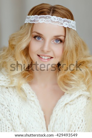 A very gentle portrait of beautiful girl blonde with blue eyes in a warm white knitted sweater, close-up