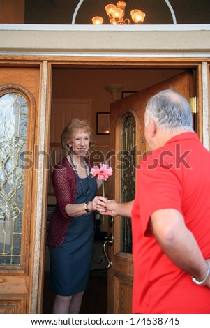 A very handsome and romantic man surprises his gorgeous wife with flowers and candy for Valentines Day at the front door. The perfect Valentines Day image for all your senior citizen love needs.  - stock photo