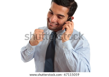A very happy businessman or salesman on a telephone call and making a fist of success or achievement.  Sales deal, new job, promotion etc. - stock photo