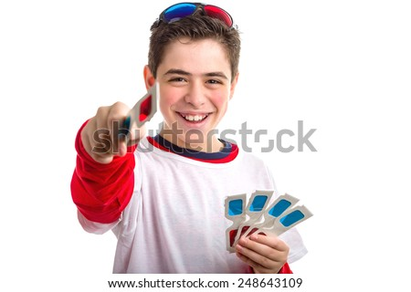A very happy Caucasian smooth-skinned boy wears a pair of black 3D Cinema paper eyeglasses on head with red and blue lenses and holds 4 white googles with left hand  while offering one with right hand - stock photo