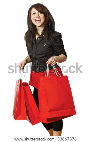A very happy shopping girl holding bags and smiling wildly about her rabid consumerism. - stock photo