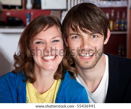 A very happy young hipster couple sitting toether - stock photo