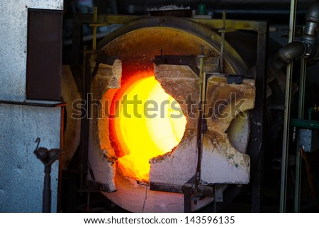 A very hot glassblowing furnace kiln is heating up ready for the molten glass. - stock photo