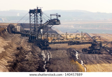 A very large bucket-wheel excavator and conveyor belt in a brown-coal mine - stock photo